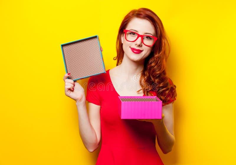 Foto av den härliga unga kvinnan som öppnar den gulliga gåvan på wonderfuen arkivfoto