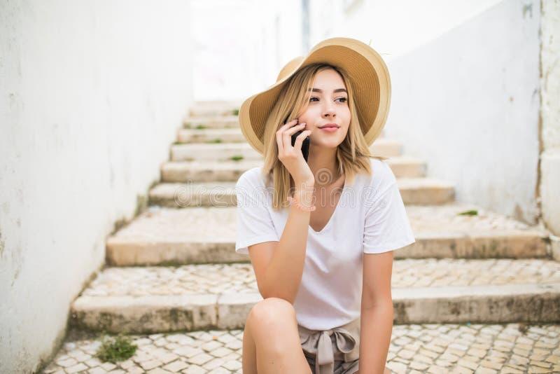 Foto av den härliga unga kvinnan som sitter på gatatrappa på sommardag och har mobil konversation på smartphonen royaltyfri fotografi