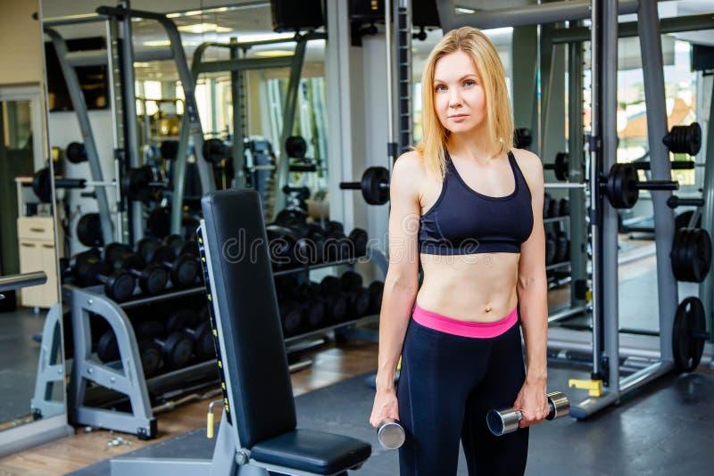 Foto av den härliga unga sportiga kvinnan Konditionflickautbildning med hantlar i sportklubba med övningsutrustningar royaltyfri fotografi