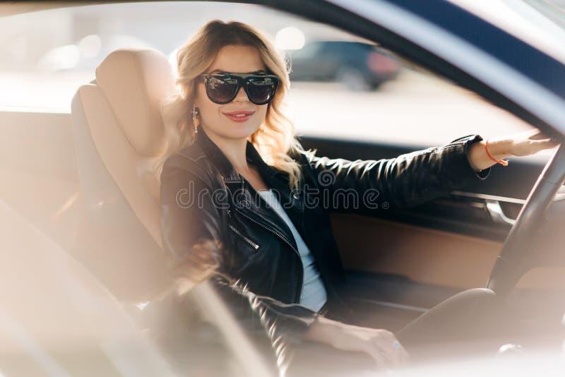 Foto av den långhåriga blondinen med lockigt hår i svarta exponeringsglas som sitter i svart bil royaltyfria bilder