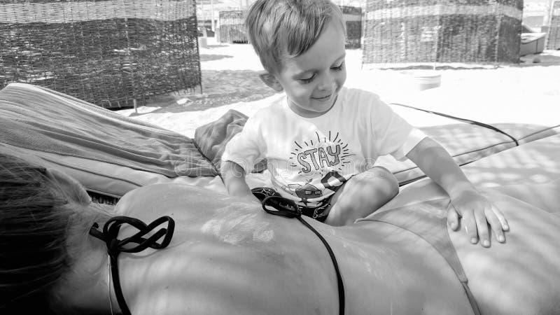 Foto av den lilla litet barnpojken som applicerar sunscreenkr?m p? m?drar som ligger tillbaka p? soldagdrivare p? havsstranden arkivbilder