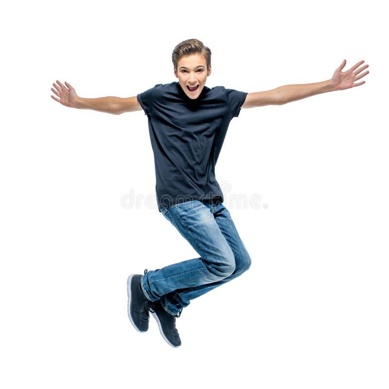 Foto av den lyckliga banhoppningen för tonårs- pojke med händer upp arkivfoto