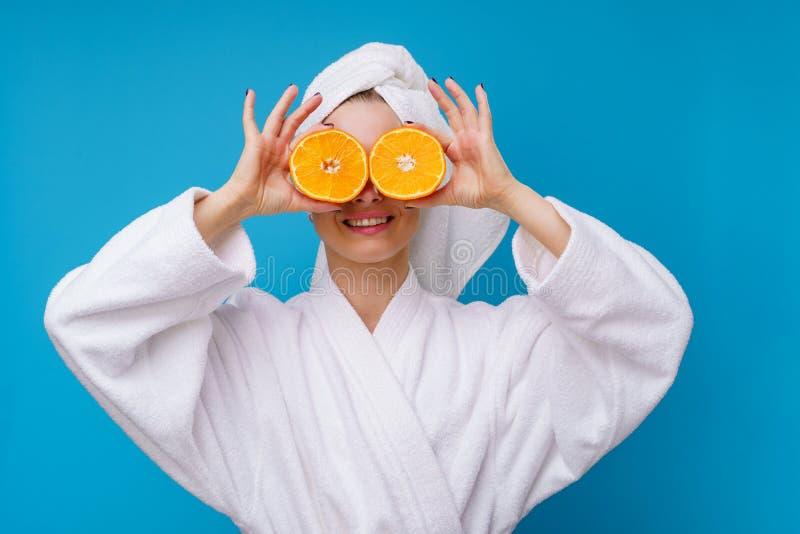 Foto av den lyckliga blonda flickan med apelsinen på ögat royaltyfri fotografi