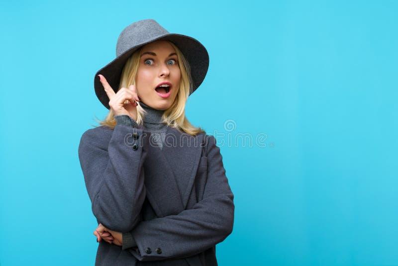 Foto av den lyckliga blonda flickan med hatten som pekar upp fingret royaltyfria foton