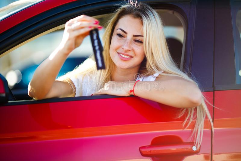 Foto av den lyckliga blonda flickan med tangenter som sitter i röd bil med det öppna fönstret royaltyfri bild