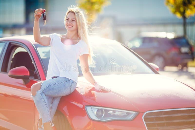 Foto av den lyckliga blonda flickan med tangenter som står nära den röda bilen på sommardag royaltyfria foton