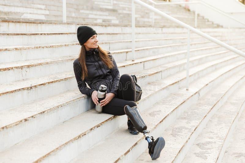 Foto av den lyckliga handikappade kvinnan i svart sportswear med prosth arkivbild