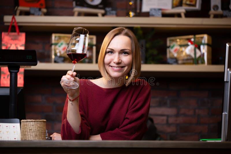 Foto av den lyckliga kvinnasäljaren med vinexponeringsglas som står bak kassaapparaten arkivfoto