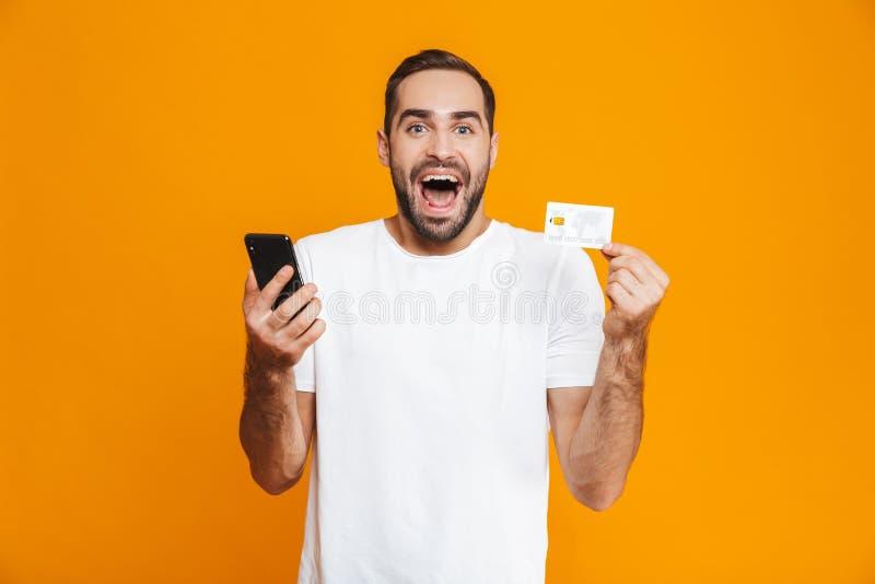 Foto av den lyckliga man30-tal i innehavsmartphone och kreditkort för tillfälliga kläder som isoleras över gul bakgrund royaltyfri fotografi