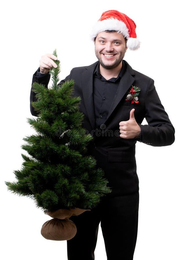 Foto av den lyckliga mannen i jultomtenhatt med julgranen arkivbilder