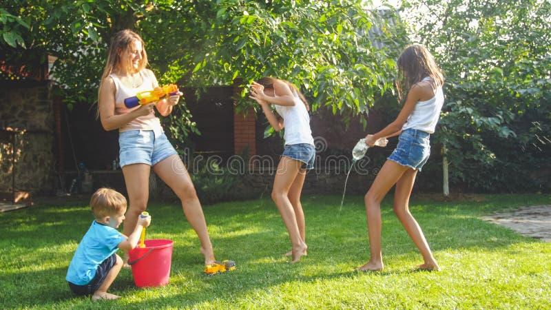 Foto av den lyckliga skratta familjen som plaskar vatten med vattenvapen och trädgårdslangen på trädgården Folk som spelar och ha royaltyfri fotografi