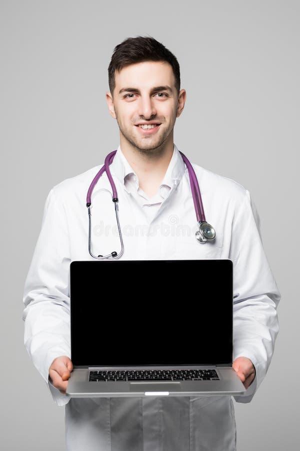 Foto av den manliga doktorn och att le till kameran och innehavet en bärbar datordator för att den tomma skärmen ska tillfoga din arkivfoto