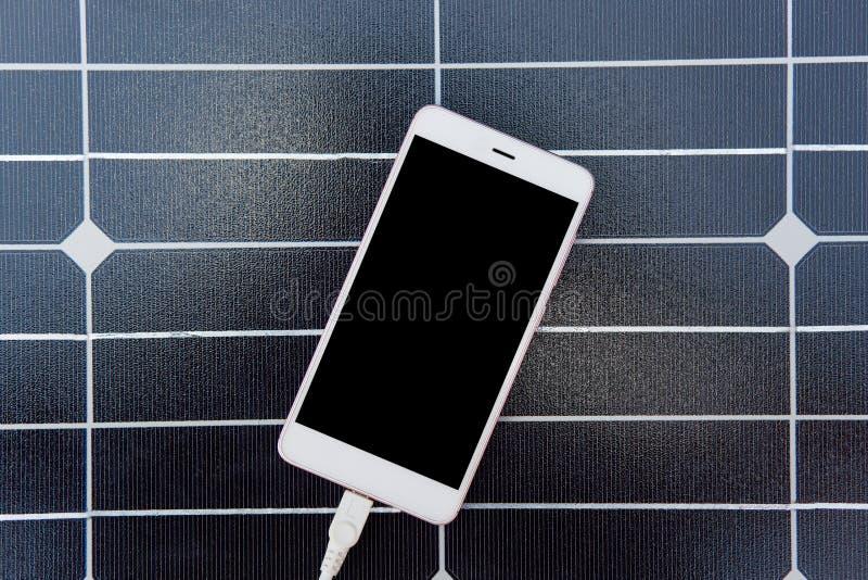 Foto av den moderna apparaten som laddar via USB som ligger på solenergipanel, bästa sikt av smartphonen med vit cabel förbindels arkivbilder