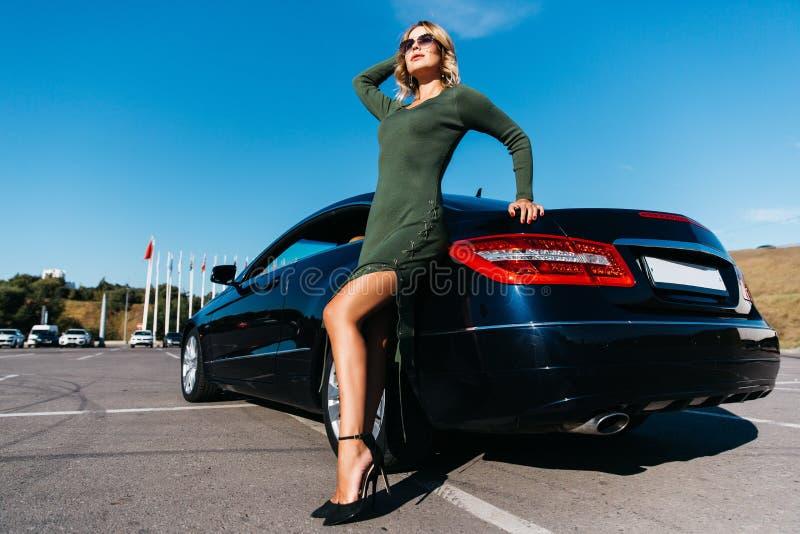 Foto av den sexiga blonda kvinnan i solglasögon i långt klänninganseende nära den svarta bilen med den öppna dörren royaltyfri bild