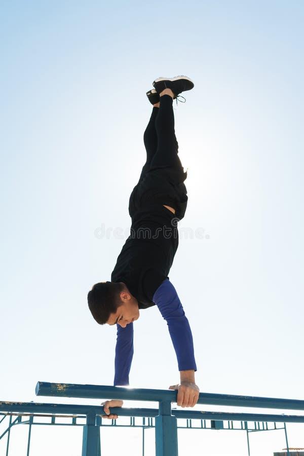 Foto av den sportiga grabben som gör akrobatik på horisontalgymnastisk stång under morgongenomkörare vid sjösidan arkivbilder