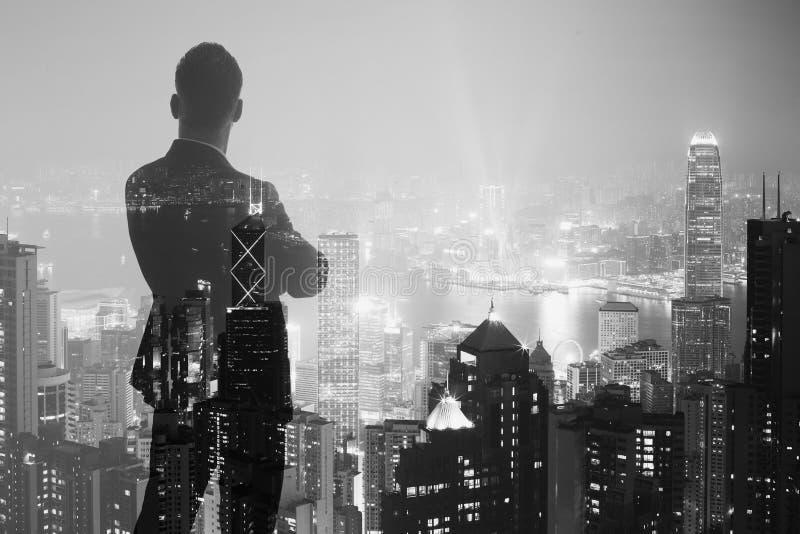 Foto av den stilfulla vuxna affärsmannen som bär den moderiktiga dräkten och ser nattstaden Dubbel exponering, modern stad b för  arkivbilder