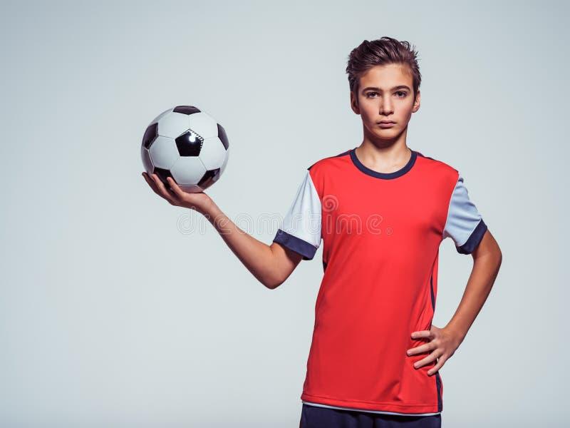 Foto av den tonåriga pojken i hållande fotbollboll för sportswear royaltyfri bild