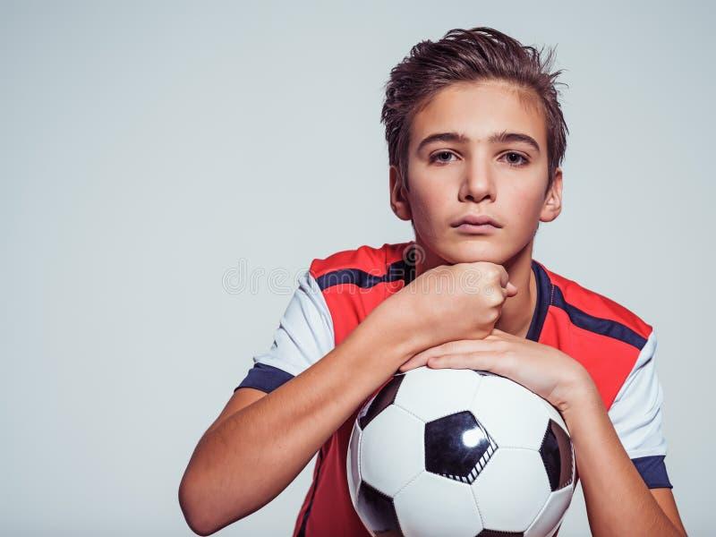 Foto av den tonåriga pojken i hållande fotbollboll för sportswear arkivfoton
