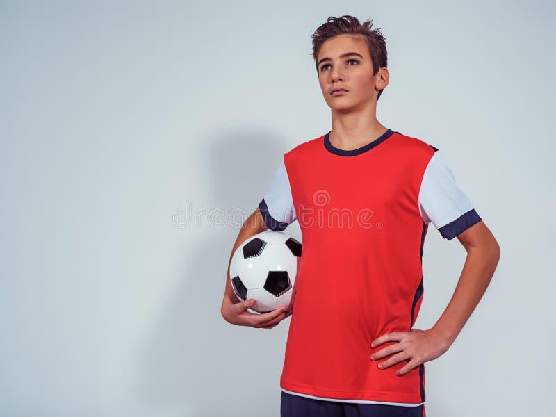 Foto av den tonåriga pojken i hållande fotbollboll för sportswear arkivfoto