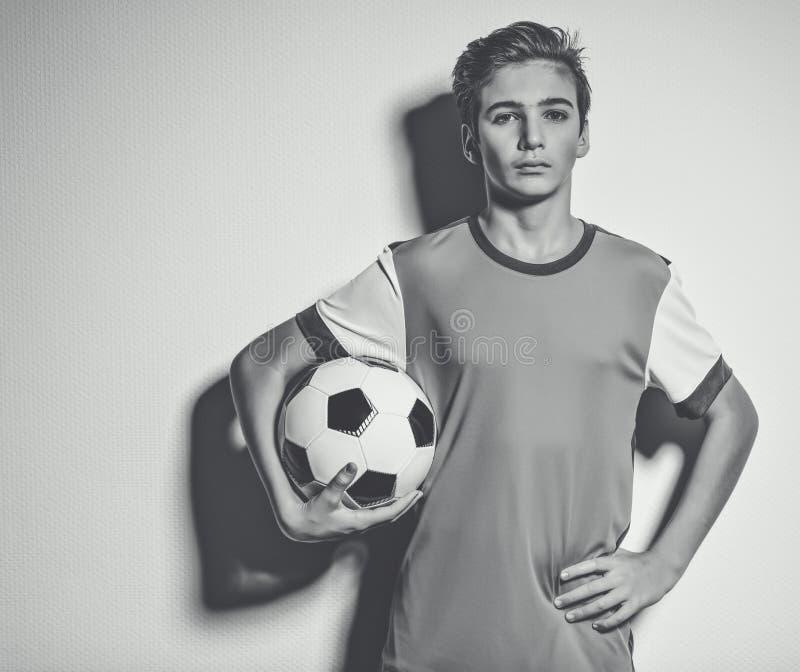Foto av den tonåriga pojken i hållande fotbollboll för sportswear royaltyfri foto