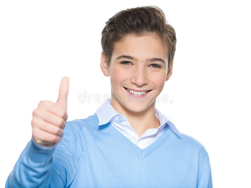 Foto av den tonårs- pojken med tummen upp arkivbild