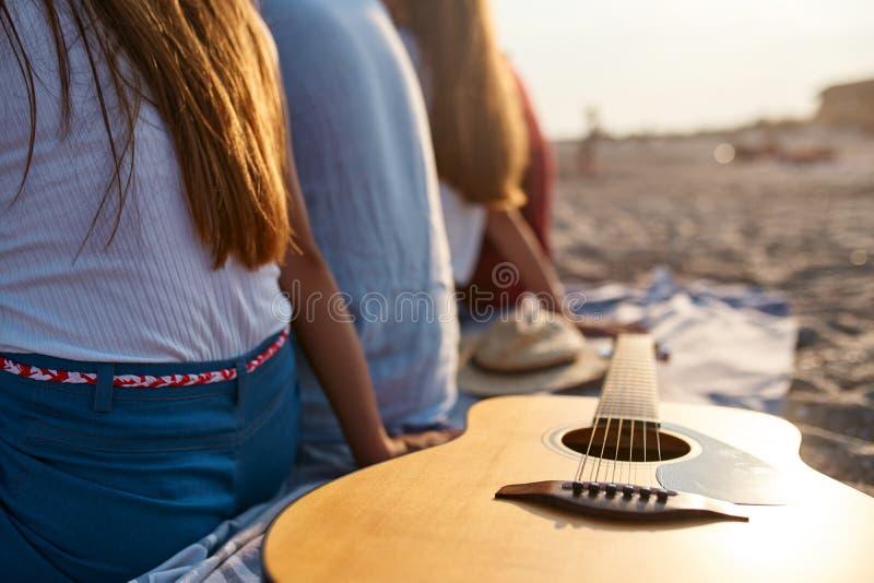 foto av den tr?akustiska gitarren p? strandhandduken Tillbaka sikt av gruppen av v?nner som tillsammans sitter p? vit sand royaltyfri bild