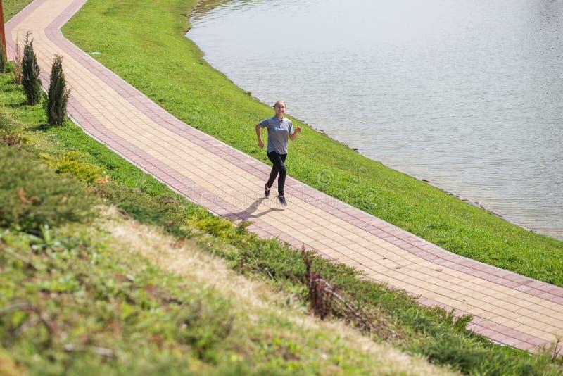Foto av den unga blonda kvinnan som gör rinnande aktiviteter royaltyfri bild