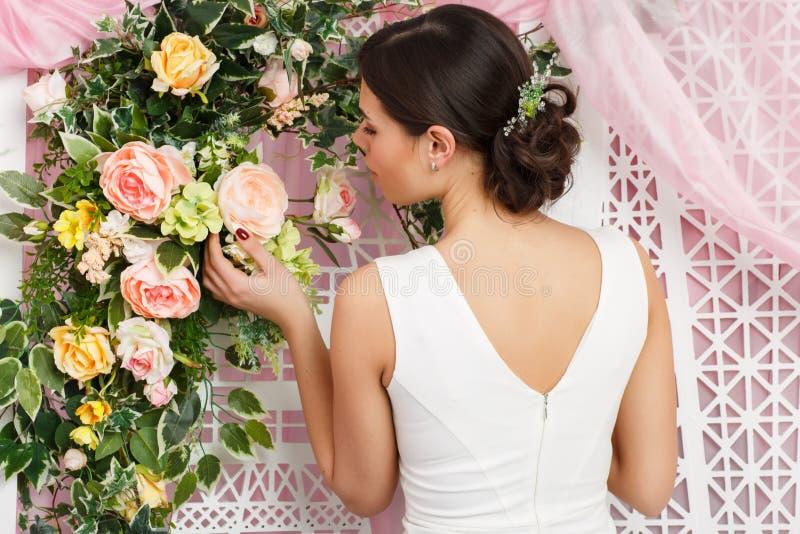 Foto av den unga brunetten i den vita klänningen på bakgrund av blommor royaltyfria bilder