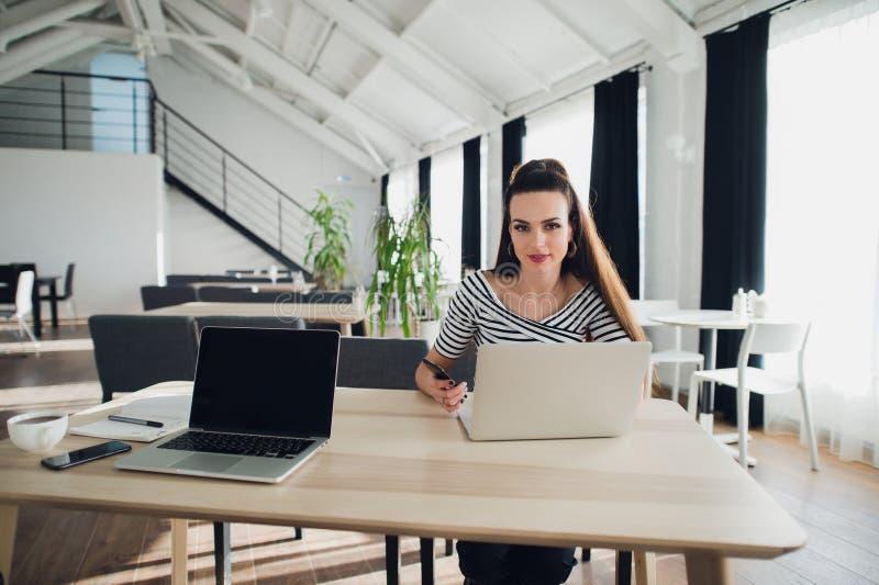 Foto av den unga gladlynta damen som i regeringsställning sitter coworking, medan genom att använda bärbar datordatoren som prata royaltyfri foto