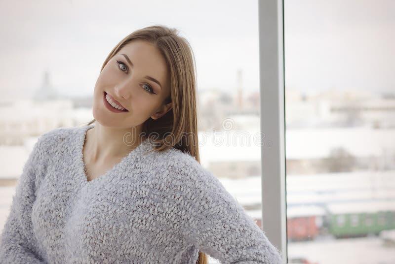 Foto av den unga härliga lyckliga le kvinnan med långt hår nära fönstret fotografering för bildbyråer