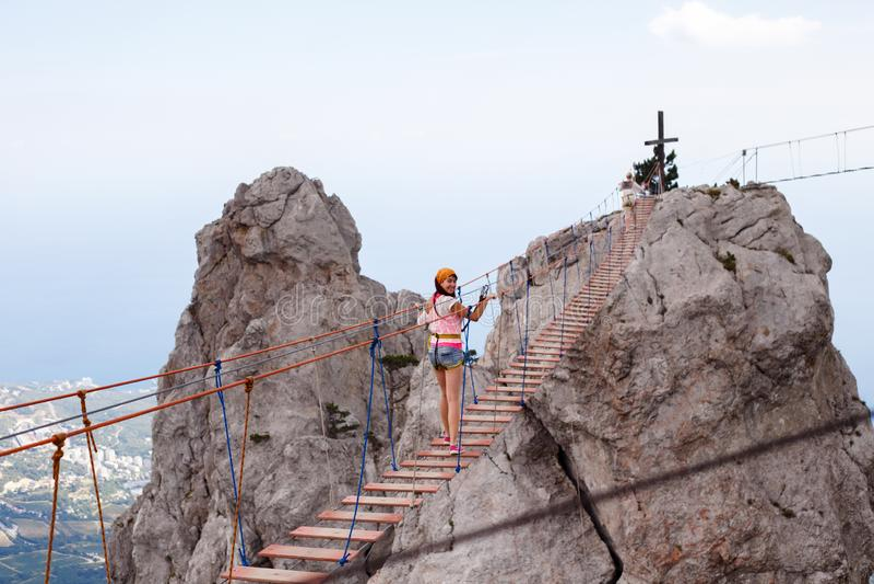 Foto av den unga kvinnan som g?r upp t-repstege mot klippan arkivbilder