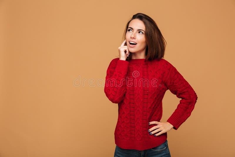 Foto av den unga nätta tänkande kvinnan i röd stucken tröjablick royaltyfri fotografi