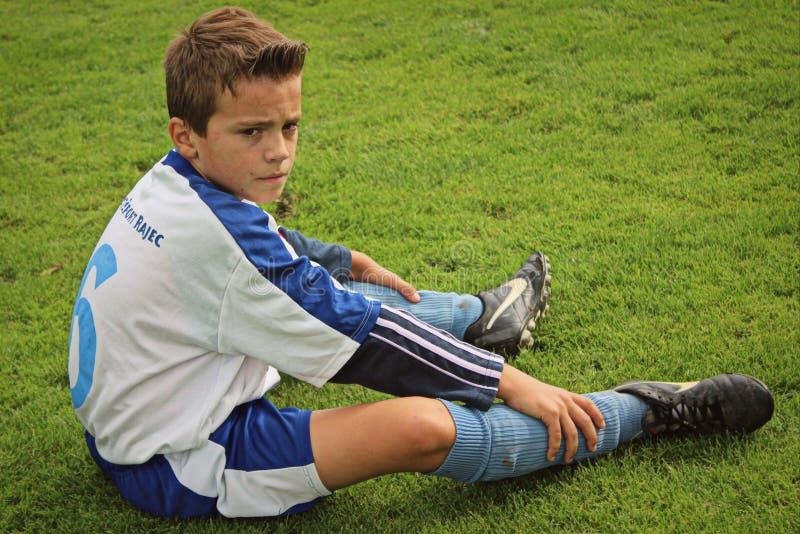 Foto av den unga pojken som är koncentraten för hans fotbollsmatch royaltyfri foto