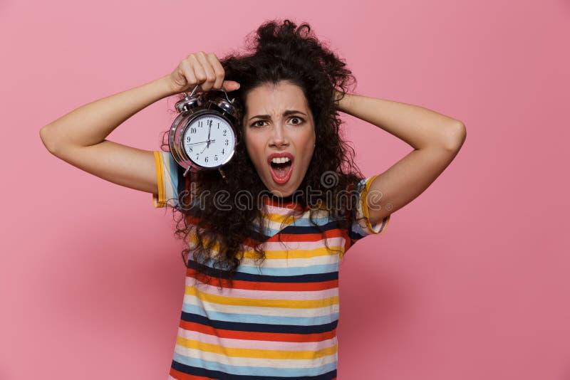 Foto av den upphetsade kvinna20-tal med innehavringklockan för lockigt hår, arkivbild