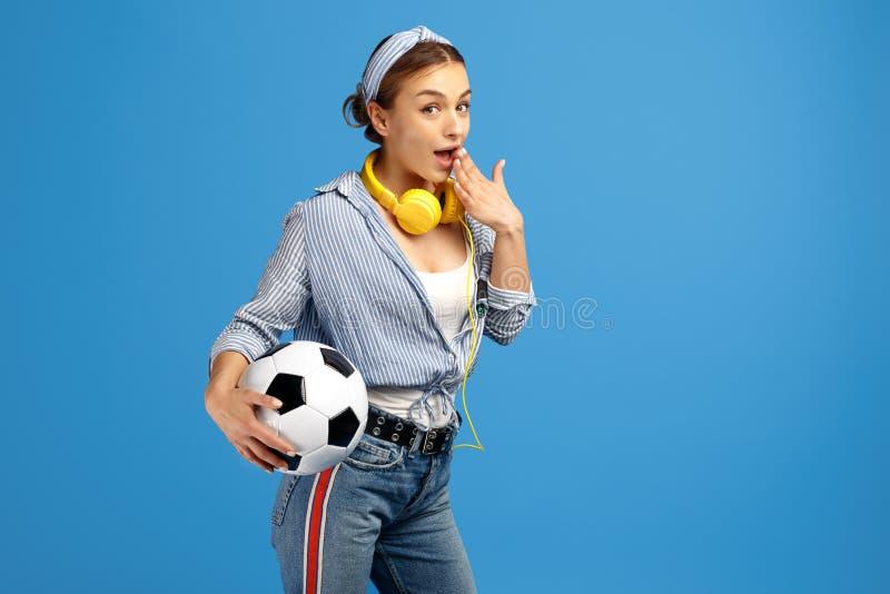 Foto av den upphetsade unga kvinnan med den gula encentmyntet eller skateboarden, fotbollbollen och hörlurar över blå bakgrund arkivbilder