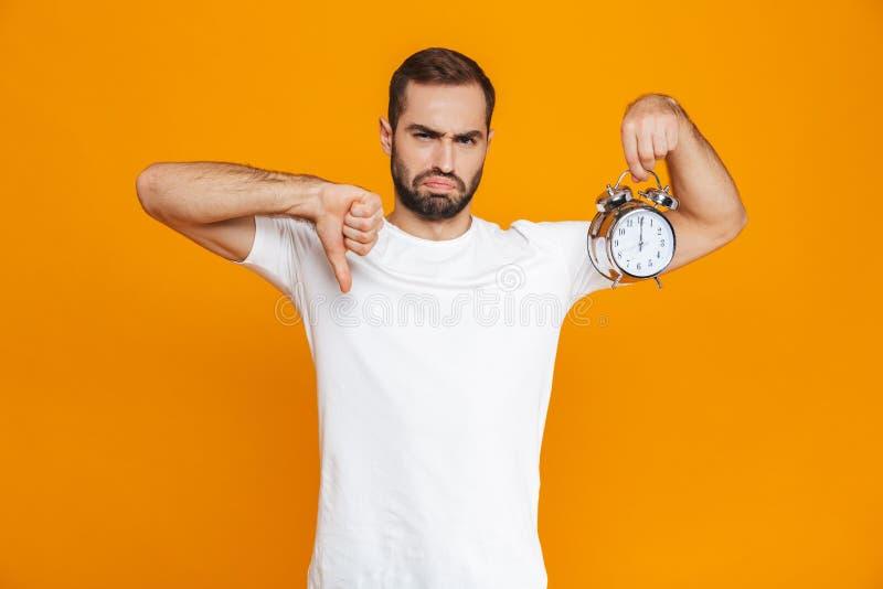 Foto av den upprivna man30-tal i innehavringklocka för tillfälliga kläder som isoleras över gul bakgrund arkivfoton