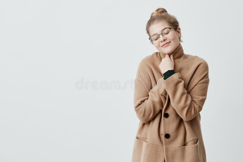 Foto av den vilsamma kvinnan med blont hår i fnuren som slår sig in i laget som har ärligt och tillfredsställt leende som stänger arkivbilder