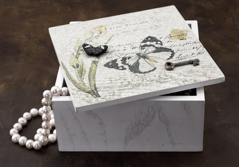 Foto av den vita smyckenasken som isoleras på brun bakgrund royaltyfria foton