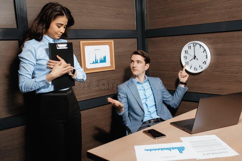 Foto av det ilskna unga framstickandepunktfingret på klockan i modernt kontor Ung kvinna som är sen på arbete royaltyfri fotografi