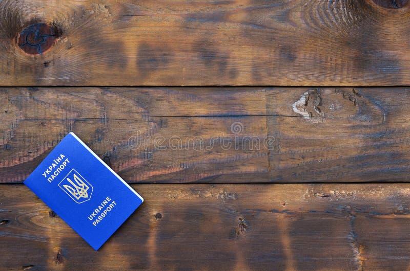 Foto av det ukrainska utländska passet som ligger på en mörk träyttersida Begreppet av introduktion av detfria loppet för Ukraini arkivbilder
