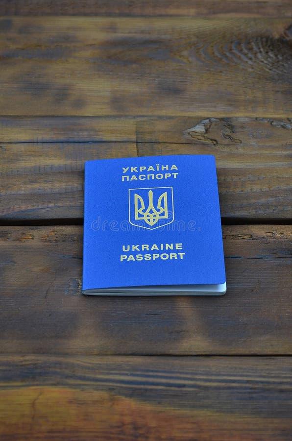 Foto av det ukrainska utländska passet som ligger på en mörk träyttersida Begreppet av introduktion av detfria loppet för Ukraini royaltyfria bilder