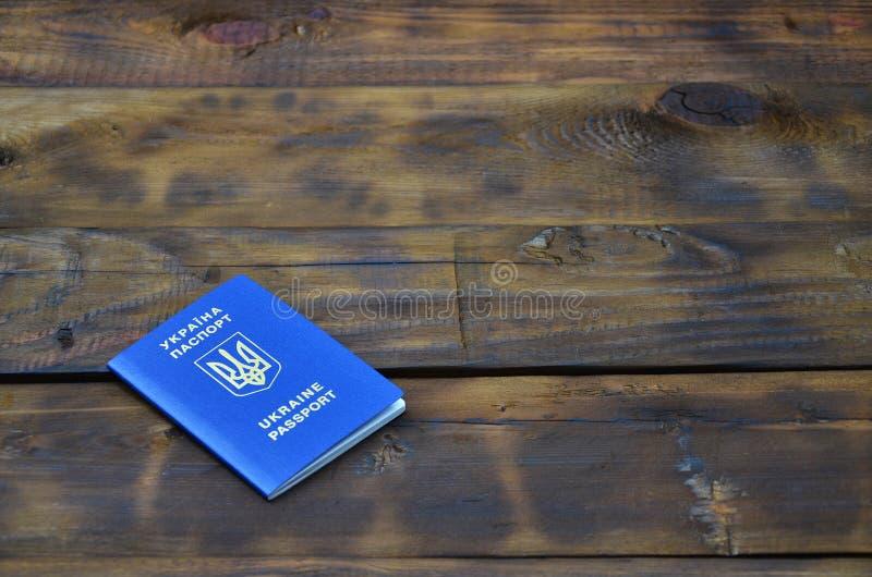 Foto av det ukrainska utländska passet som ligger på en mörk träyttersida Begreppet av introduktion av detfria loppet för Ukraini royaltyfria foton