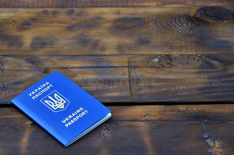 Foto av det ukrainska utländska passet som ligger på en mörk träyttersida Begreppet av introduktion av detfria loppet för Ukraini royaltyfri fotografi