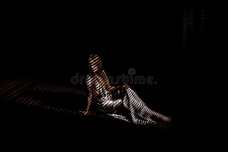 Foto av en flicka i ljuset till och med rullgardinerna arkivfoto