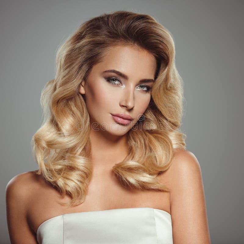 Foto av en härlig ung blond kvinna med lockigt hår arkivfoton