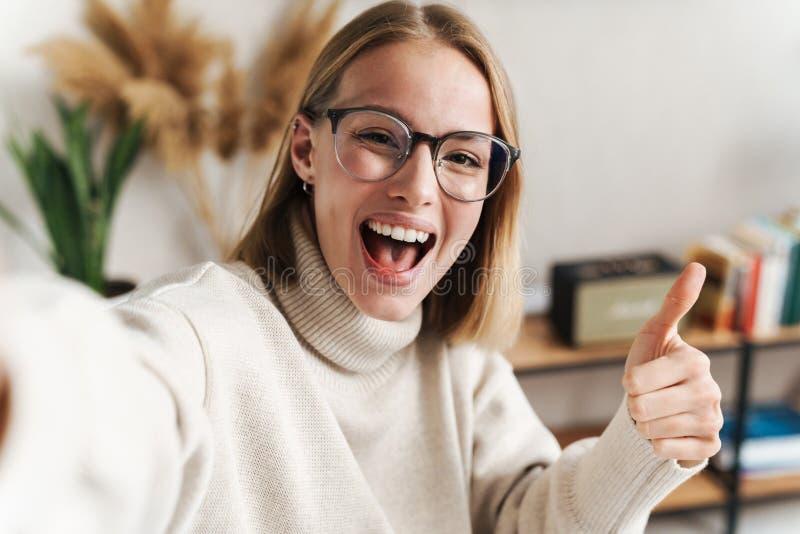 Foto av en leende attraktiv kvinna som tar selfie och visar tummen upp royaltyfri foto