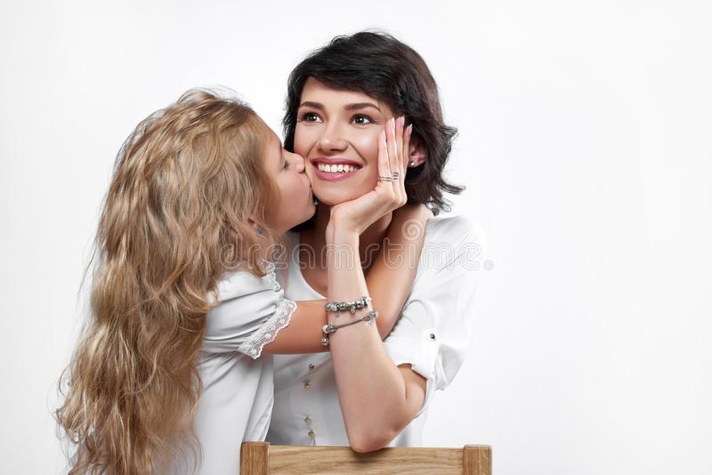 Foto av en lycklig moder med en daugher, som kysser henne royaltyfri fotografi