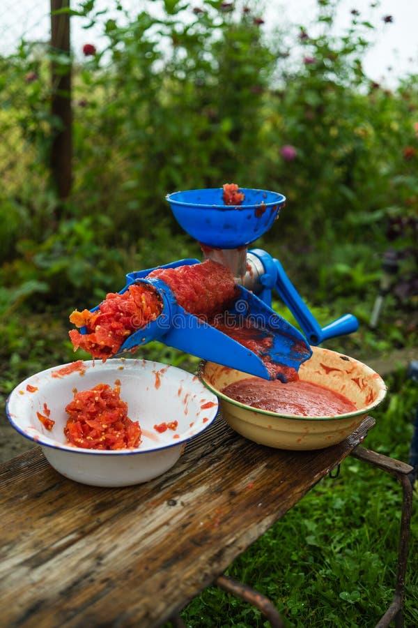 Foto av en manuell tomat-molar Nya tomater, för att förbereda handgjord tomatsås royaltyfri foto