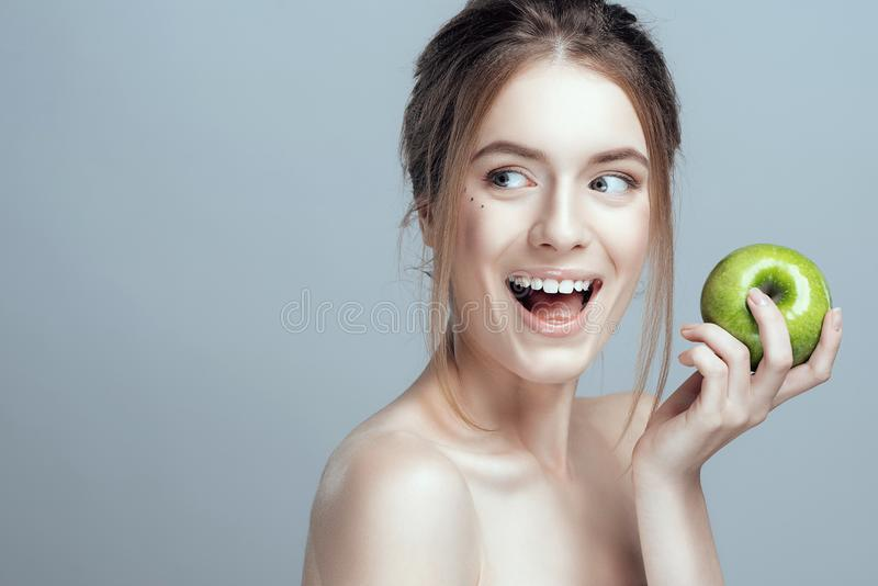 Foto av en närbild av en härlig flicka med ett grönt äpple i hennes hand Hon har rent och även hud royaltyfria bilder