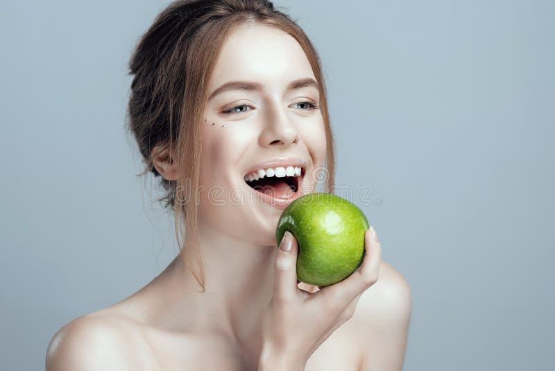 Foto av en närbild av en härlig flicka med ett grönt äpple i hennes hand Hon har rent och även hud royaltyfri bild